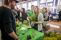 A visitor with her free flowers speaks with an UrbanStems employee at the TechDay New York event on Thursday, April 23, 2015. Thousands attended to seek jobs with the startups and to network with their peers. TechDay bills itself as the world's largest startup event with over 300 exhibitors. (© Richard B. Levine)