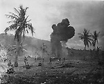 Marine infantry advancing behind tanks along the norther curve of Magicienne Bay on Saipan.