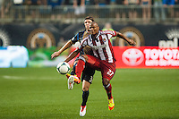 Jose Correa (27) of CD Chivas USA is marked by Jeff Parke (31) of the Philadelphia Union during a Major League Soccer (MLS) match at PPL Park in Chester, PA, on July 12, 2013.