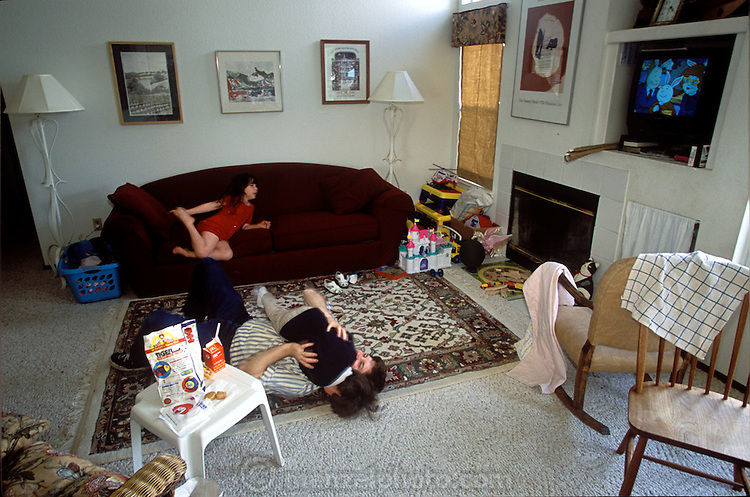 (MODEL RELEASED IMAGE). Craig Caven enjoys a wrestling match with his son, while Andrea is watching cartoons on television. They are surrounded by debris from the Happy Meals they purchased at the drive-thru window of a McDonald's in Napa, California, on the way home from the weekly shopping expedition to Raley's, a California grocery chain. The high school where Craig teaches is on break this week, so the children are out of daycare and home with Dad. (Supporting image from the project Hungry Planet: What the World Eats.)