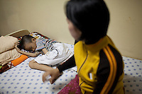 Thang, 9,  and his mother Tuyet wait for his heart surgery at the hospital in Ho Chi Minh City, Vietnam..---..Nguyen Van Thang is nine-years-old and just finished second grade. He lives in the coastal town of Nha Trang with his mother, grandmother, and 10-month-old brother. Thang's father, Bui Van Tri, spends much of his time away from his family, as he is a fisherman and works up and down the coastline. His income is about 400,000VND (~$23USD) per month; however, this salary is seasonal and there are months when he earns nothing at all. ..Thang's mother, Nguyen Thi Bach Tuyet, is 31-years-old and is a housewife. She cannot work as she must look after Thang, his brother, and his grandmother. Therefore, the family of five is solely dependent on Thang's father's income. The family lives in a lean-to extension of Thang's uncle's house that is just eight square meters with a tin roof, cement floor, and brick walls...Thang suffers from Ventricular Septal Defect (VSD), a common congenital heart defect (CHD) that occurs when there is a hole in the wall between the right and left ventricles of the heart. Symptoms of VSD include shortness of breath, fast heartbeats, loss of appetite, poor weight gain, chest pain, and discolored blue skin. In addition, other areas of the child's development such as physical growth and brain development are affected if VSD is left untreated, and the child also has a high chance of developing irreversible pulmonary hypertension...Thang was diagnosed with VSD when he was just two-months-old. He and Tuyet, his mother, made the arduous 10-hour trek from Nha Trang to the Heart Institute in Ho Chi Minh City at least five times over the course of his life, and the diagnosis was always the same: Surgery, or else he would die. Lifesaving surgery, however, was out of the question as it cost $3,100USD--a sum that was beyond anything Thang's family could scrape together. After each hospital visit Tuyet would make the long bus journey back to Nha Trang wit