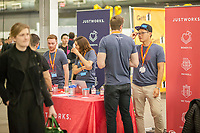 Workers from Justworks speak to attendees at the TechDay New York event on Tuesday, April 18, 2017. Thousands attended to seek jobs with the startups and to network with their peers. TechDay bills itself as the U.S.'s largest startup event with over 500 exhibitors. (© Richard B. Levine)
