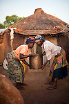 Most of the residents of the Gambaga camp for alleged witches are elderly and find manual work difficult. Here  a resident helps her neighbour to lower a bucket of water brought from the communal tap.