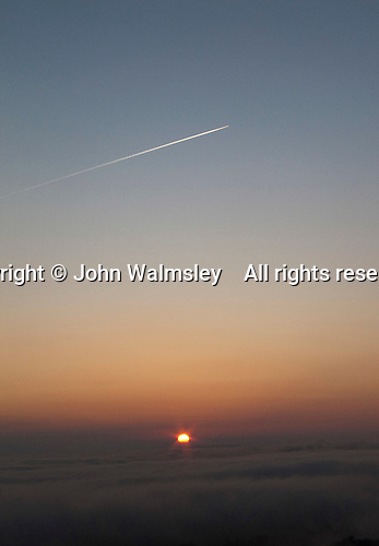 Contrails or water condensation trails from an aircraft's jet engines visible high above some almost ground level stratus clouds and a winter sunset in rural Surrey.