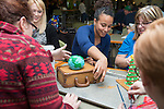 (Left to Right) Ashley Beatty- Smith, Charisa King and Lori Collins construct the Global Opportunities gingerbread house. Photo by Ben Siegel.