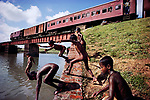 Children swim along the Dhaka-Chittagong rail line, Bangladesh, 1982.<br />