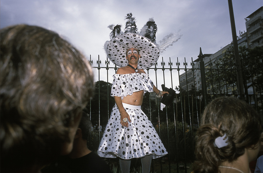 Before one of three parades formed by the Banda de Ipanema in Rio de Janeiro, a transvestite echoes Cruella de Ville for curious onlookers.