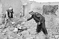 Two ethnic Hazara men clear the rubble from a destroyed school near Bamiyan, Afghanistan on June 30, 2002. Many schools were destroyed during Taliban rule, leaving the war-ravaged country with yet another massive reconstruction task.