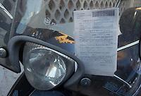 Motorino in doppia fila e in divieto di sosta, con relativa multa..Scooter in two rows and no parking, and the contravention.