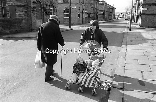 Saltaire near Bradford West Yorkshire England 1981. Young mother pushing childs double buggie along the road. Does not use pavement because its not smooth. Same applies to old man. World Heritage Site