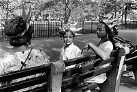 USA. New York. Battery park. Three generations of afro american women (grandmother, daughter and mother) wear on their heads a plastic crown with an american flag which celebrates the 100th anniversary of the Statue of Liberty. 25.06.86 © 1986 Didier Ruef