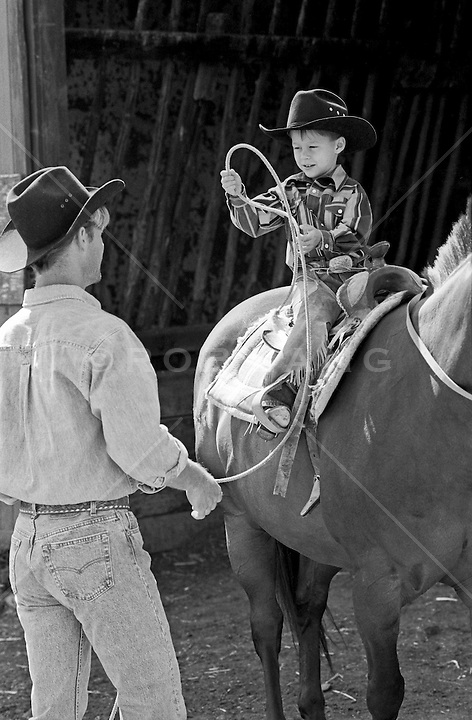 cowboy teaching a boy how to make a lasso