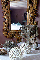 In front of an ornate antique mirror in the rose-pink salon an enchanting still-life of contemporary ceramics, antique figurines and natural objects