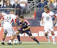New England Revolution midfielder Kelyn Rowe (11) dribbles on offense. In a Major League Soccer (MLS) match, the New England Revolution (blue) defeated D.C. United (white), 2-1, at Gillette Stadium on September 21, 2013.