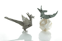 New York, NY, USA - November 4, 2011: Three Origami creations photographed in studio. The wyvern on the left is designed by John Montroll and folded from one piece of paper. The dragon on the right is designed by Kunihiko Kasahara and folded from one square of paper without cuts. The polyhedral  Ishibashi ball is folded from more than one piece of white paper. Esmé Cribb folded all three pieces.