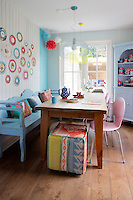 The family kitchen is furnished with a blue-painted bench decorated with coloured cushions, made by friends, who also made the pouffe from old blankets