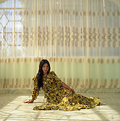 "A Roma girl sits, posing on the floor of her friends house, imitating images of Western models that she has seen. The girls of the camp prefer to be seen and photographed as ""western women"" rather than ""gypsy/Roma women"".."