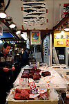 """A wholesaler at the world's biggest fish Market in Tsukiji, Tokyo displays pieces of whale meat at his store at the market. More than 2,300 tons of fish -- about one-third of the total consumed in Japan -- passes through Tsukiji each day and the market offers more than 450 varieties of marine products. The market, which dates back almost 75 years, is slated to move to a high-tech site on a man-made island in Toyosu, which is well-documented as being contaminated with benizine. Not that Tsukiji is much better off -- many buildings in the aging site are stuffed with asbestos. """"Choose your poison,"""" says one Tsukiji official. The new site, which the government plans to be readied by 2012, will be significantly larger, with more room for off-loading and for sellers to display their goods. The current location, says one official, is too cramped and collisions between motorised carts and pedestrians means accidents occur almost daily. Meanwhile, with fish sales down, it is becoming more difficult to justify Tsukiji's prime location and property developers are keeping a close watch on Tsukiji land, which is just a few blocks from the ritzy Ginza district of Tokyo, where per-meter land prices are among the highest in the world...The move to the new Toyosu location, meanwhile, has been at the center of heated debate -- clean-up operations alone are estimated to cost ¥67 billion (around US$660 million), with a further ¥450 billion to build a new marketplace. Big wholesalers favour the move, but the 1,600-plus merchants mostly are against it. Yoshiharu Kikuraku, a Tsukiji storeowner who began working at the market 60 years ago, expresses bewilderment at the plans, saying that the name Tsukiji itself has become synonymous with the world's best and most eclectic selection of fish. """"This place has a long tradition. Why break it and start from scratch all over again?"""" he says. """"Government officials only think what's best for themselves, nobody else."""" Indeed, many companies dealing"""
