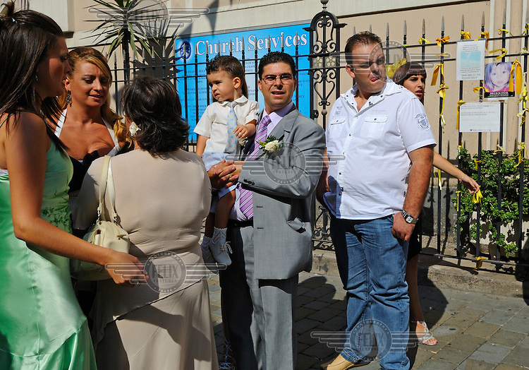 Guests gathering before a Catholic wedding at the Cathedral of St Mary the Crowned on Main Street. The population is 86% Catholic, and the territory has its own Bishop.