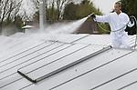 Foto: VidiPhoto<br /> <br /> HUISSEN - Het 8000 vierkante meter grote glazen dak van cactuskweker Van Blitterswijk uit Huissen bij Arnhem krijgt maandag een witte beschermlaag tegen de zon. De grootste 'witwassers' van de Betuwe, Frank en Berry Kuster, komen van april tot en met juli handen tekort om aan de grote vraag aan de zonwerende en afbreekbare krijtlagen te voldoen. Om bloemen en planten te beschermen tegen te felle instraling van de zon en te snelle warmteopbouw in lente en zomer, moet er ieder voorjaar een witte beschermlaag worden aangebracht. Bij de kleinere kassen, zoals in Huissen en omgeving, gebeurt dat nog een de ouderwetse manier met de hand. De broers Kuster uit Bemmel zijn daarin gespecialiseerd. Een nat voorjaar betekent dat het aanbrengen van de krijtlagen enkele keren in het seizoen herhaald moet worden. Jaarlijks spuiten de Kusters zo'n 40 ha. aan kasdekken.