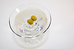Martini glass with olives from above with bubbles