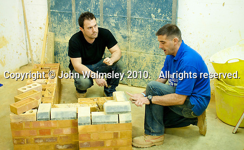 Instructor (blue top) and student on a bricklaying course.  Able Skills in Dartford, Kent, runs courses in construction industry skills like, bricklaying, carpentry and tiling.