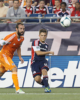 New England Revolution midfielder Kelyn Rowe (11) passes the ball.  In a Major League Soccer (MLS) match, Houston Dynamo (orange) defeated the New England Revolution (blue), 2-1, at Gillette Stadium on July 13, 2013.