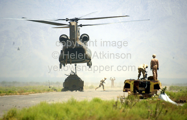 US CHINOOK MOVES BROKEN TANK FROM RUNWAY FOR TARGET PRACTISE, AT BAGRAM AIRBASE, AFGHANISTAN...PICTURE: HELEN ATKINSON
