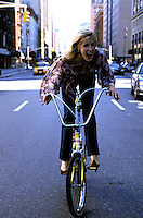 Woman on banana seat bicycle in middle of street