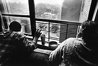 "USA. New York City. Spanish Harlem. Richie (L) and her mother Pat (R) are looking outside at 110 Street. Plastic glass and ashtray. The Puerto Rican family lives below the poverty line and receives public assistance (AFDC, Home Relief, Supplemental Security Income and Medicaid). The family resides in units managed by the New York City Housing Authority (NYCHA) which provides housing for low income residents. NYCHA administers rental apartments in facilities, popularly known as ""projects"". Spanish Harlem, also known as El Barrio and East Harlem, is a low income neighborhood in Harlem area. Spanish Harlem is one of the largest predominantly Latino communities in New York City. 20.10.86 © 1986 Didier Ruef .."