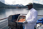 Alaska, Cruising the Southeast wilderness waterways on the Spirit of Discovery..Chef Robert Model Released, prepares salmon..Photo copyright Lee Foster, 510/549-2202, lee@fostertravel.com, www.fostertravel.com..