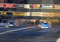 Feb 12, 2016; Pomona, CA, USA; NHRA funny car driver Alexis DeJoria (left) races alongside John Force during qualifying for the Winternationals at Auto Club Raceway at Pomona. Mandatory Credit: Mark J. Rebilas-USA TODAY Sports