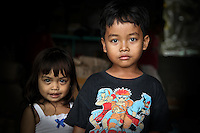 Young Balinese village children curiously looking out of their house doorway into the surrounding rice fields.