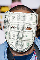 A man wore a mask made to look like it was made of 100 dollar bills in Cambridge Common during a Tax Day protest near Harvard Square in Cambridge, Mass., on Sat., April 15, 2017. The demonstrators called for President Donald Trump to release his tax returns. Trump refused to release his tax returns during the 2016 presidential campaign, in contrast to all previous major party presidential candidates, and continues to refuse to release them. The protest was part of a larger movement nationwide called Tax March.