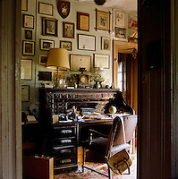 The walls of this study are covered in old family photographs, certificates and diplomas and the antique roll-top desk is cluttered with objects and papers