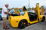 Bellmore, New York, USA. 12th June 2015. Owner Grey Cherveny, of Bay Shore, is standing at the open trunk of his modified yellow 2003 Corvette 50th Anniversary model, with Lamborghini doors (AKA vertical scissors doors and Lambo doors) and chrome trim added, an award winning car displayed  at the Friday Night Car Show held at the Bellmore Long Island Railroad Station Parking Lot. Hundreds of classic, antique, and custom cars were on view at the free weekly show, sponsored by the Chamber of Commerce of the Bellmores.