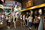 Customers walk past a popular noodle store in the trendy neighborhood of Kichijoji in Musashino City,  Tokyo, Japan on 16 Sept. 2012.  Photographer: Robert Gilhooly