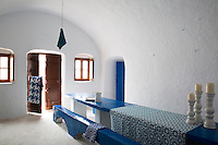 The cool vaulted entrance hall is furnished with a long blue-painted concrete table and matching bench