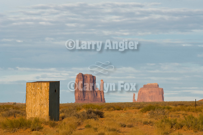 Plywood outhouse and Mitten Buttes west of Monument Valley, Ariz.