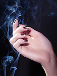 Woman's hand with fancy shiny nail polish in a stream of rising smoke on black background