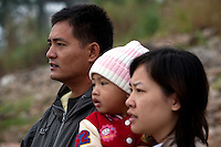 Pornlert Prompanya, 32, left, stands with his wife Ary holding their son Asia, 2, while watching a Chinese cargo ship pass by on the Mekong River in Sop Ruak, Thailand. Photo taken on Thursday, December 10, 2009. Kevin German / Luceo Images