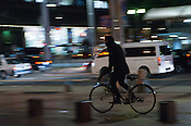 Cyclists braving the city cold at night.