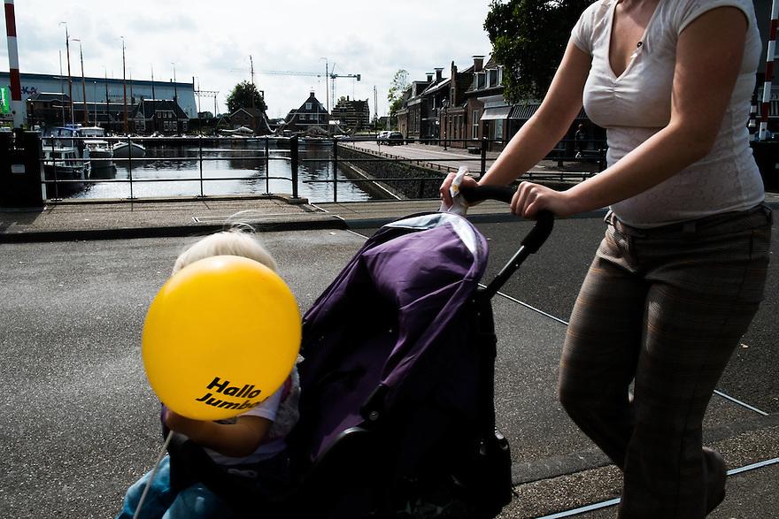 Nederland, Lemmer, 7 sept 2014<br /> Moeder met kind in kinderwagen. Kind heeft bij de Jumbo een reclameballonnetje gekregen<br />  <br /> Foto: (c) Michiel Wijnbergh
