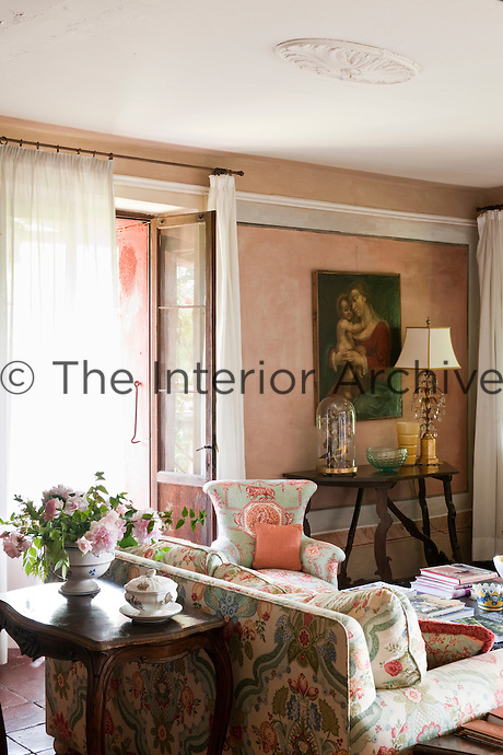 a Madonna and Child oil painting, antique tables and pale pink walls