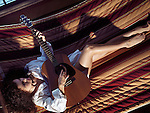 Young woman with an acoustic guitar lying in a hammock in a cozy cottage home, wearing man's shirt