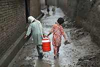 Children carrying a container of water distributed to victims of floods in Pakistan