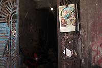 2011 Mokattam Garbage City (alla periferia del Cairo) il quartiere copto dove si vive in mezzo alla spazzatura raccolta: un manifesto con simboli cristiani appeso ad una porta.