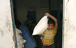 A Palestinian child carries food aid receiving from UN Relief and Works Agency (UNRWA) warehouse, in Rafah refugee camp southern the Gaza strip, Oct. 30, 2012. In the aftermath of the Israeli military Operation Cast Lead in 2008/2009, Palestinian refugees in Gaza camps need more support to reconstruct Gaza, promote economic recovery and address the long-term development needs, including infrastructure. Photo by Eyad Al Baba