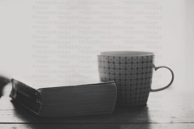 a black & white photo of a book & a cup sit on a wooden table, morning light flooding in the window behind it.