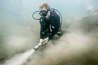 A SCUBA diver uses a water jet to push sand away from a shipwreck. (Model Released)